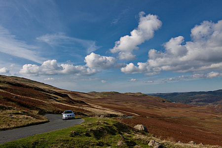 A BMW car drives along an open and twisting road in the Lake District in Cumbria, England