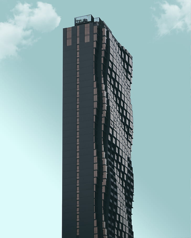 photo of black and gray curved high-rise building