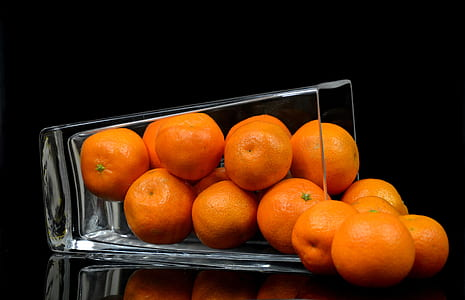 closed up photography of pile orange fruit in clear glass cup