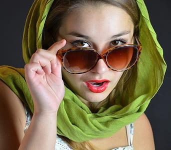 woman wearing green hijab touching oversize sunglasses