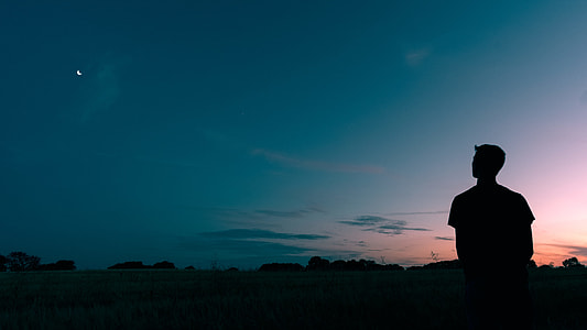 silhouette photography of man standing and starring moon