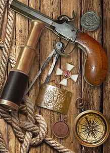 vintage pistol and gold spyglass on table