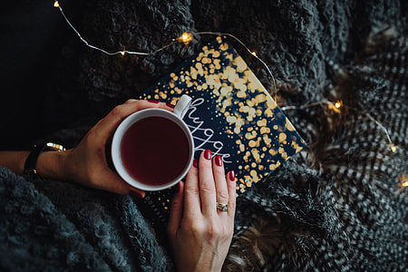 Young woman at home reading Hygge book and drinking