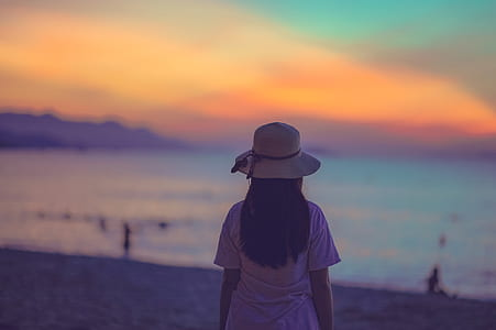 Woman in White Dress Standing Near Beach during Sunset