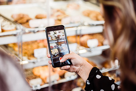 woman holding iPhone 6 capturing bread