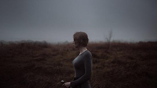 woman in grey crew-neck long-sleeved shirt standing of beige grass field