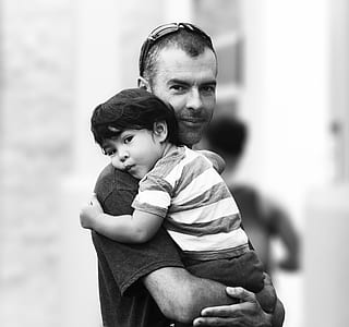 grayscale photography of man carrying baby