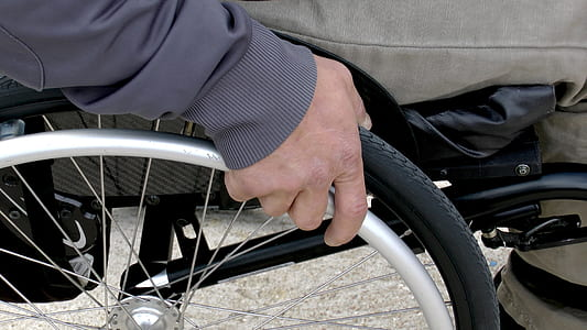 person sits on chrome-colored wheelchair