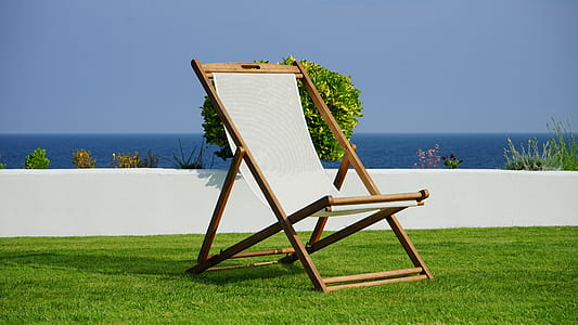 brown and white outdoor folding lounge chair under sunny sky
