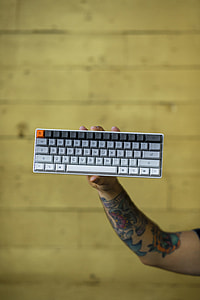 person holding grey and black computer wireless keyboard