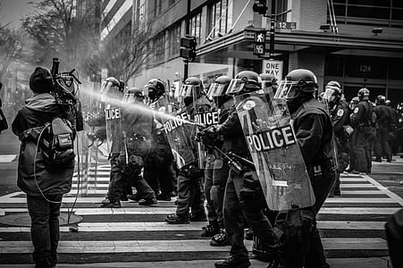 grayscale photography of police with shields stands on pedestrian lane