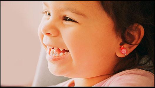 girl wearing pink earring smiling