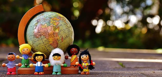 shallow focus on kids plastic toy surrounding desk globe