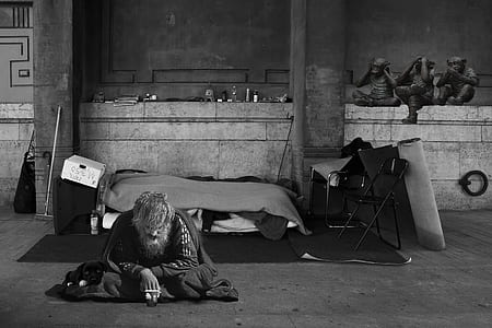 grayscale photography of man sitting on ground