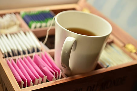 white ceramic mug with tea in brown wooden tea bag box