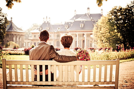 man and woman sits on white wooden outdoor bench in front of white and black house at daytime