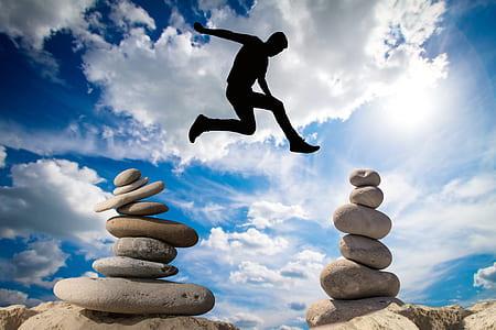 man jumping above balance stones