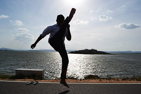 man raising his foot in the middle of the road near body of water