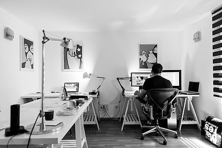 grayscale photo of man using computer