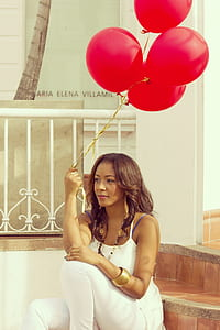 woman wearing white camisole top holding red balloon