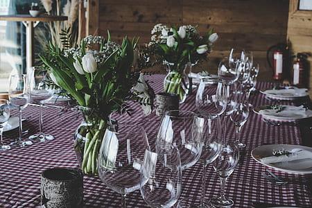closeup photo of long-stem wine glasses near ceramic plates and white petaled flowers on talbe