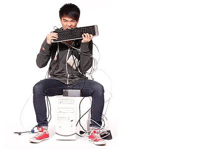 man in black hoodie biting keyboard