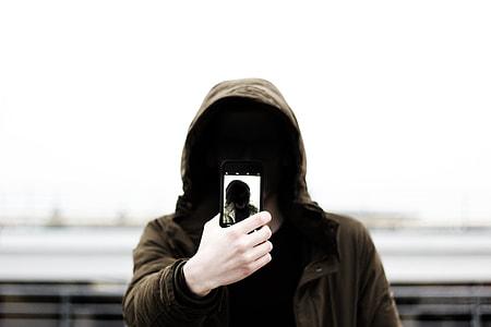 person holding phone wearing brown hoodie