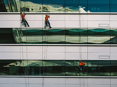 three person climbing on building at daytime