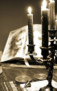sepia photography of lighted candles with candelabra near open books