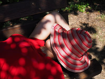 woman wearing red shirt lying on bench putting her red bucket on face