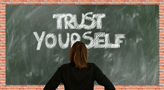 woman facing green board with trust yourself text