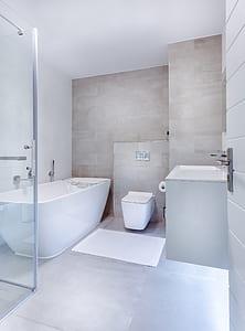 white ceramic bath tub near toiley