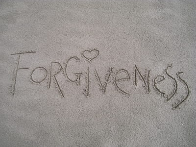 closeup photo of Forgiveness drawn in sand