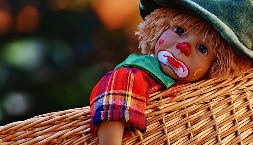 clown doll on brown wicker basket