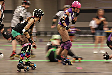 woman in pink helmet skating beside woman in green shorts