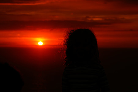person looking at setting sun
