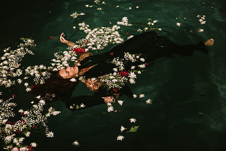fashion photography of woman in black dress floating on water