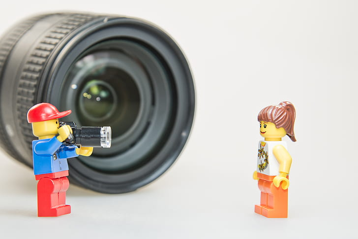 two male and female LEGO minifigures in front black camera lens