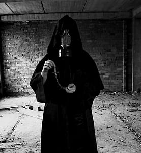 grayscale photo of person wearing black gas mask and robe