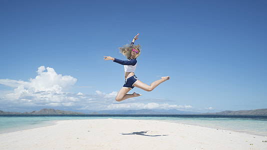 woman jumping near seashore during daytime