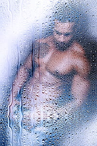 topless man viewed on glass with water droplets