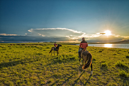 two men rides horse during golden hour