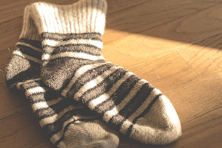 pair of white-and-black striped socks on brown surface