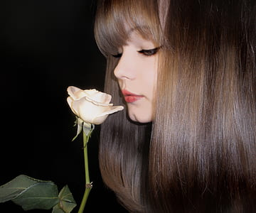 woman smelling white rose flower