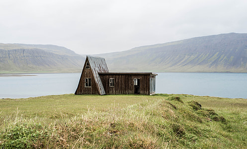 brown and gray wooden house on green grass field during day time