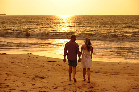 couple holding each other while walking beside beach