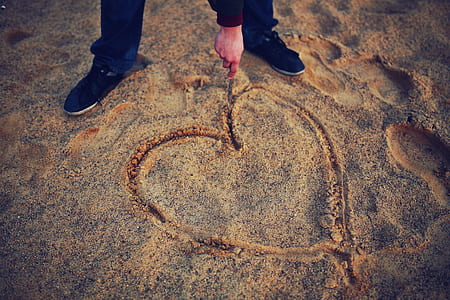 Hand drawing heart in the sand