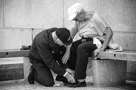 man kneeling on floor in front of woman sitting on concrete bench