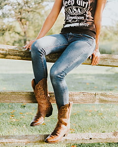 woman wearing brown cowboy boots sitting on brown wooden fence