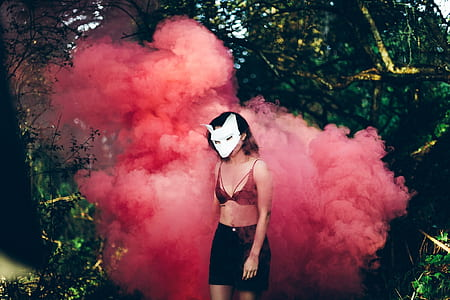 woman wearing red brassiere standing near red smoke